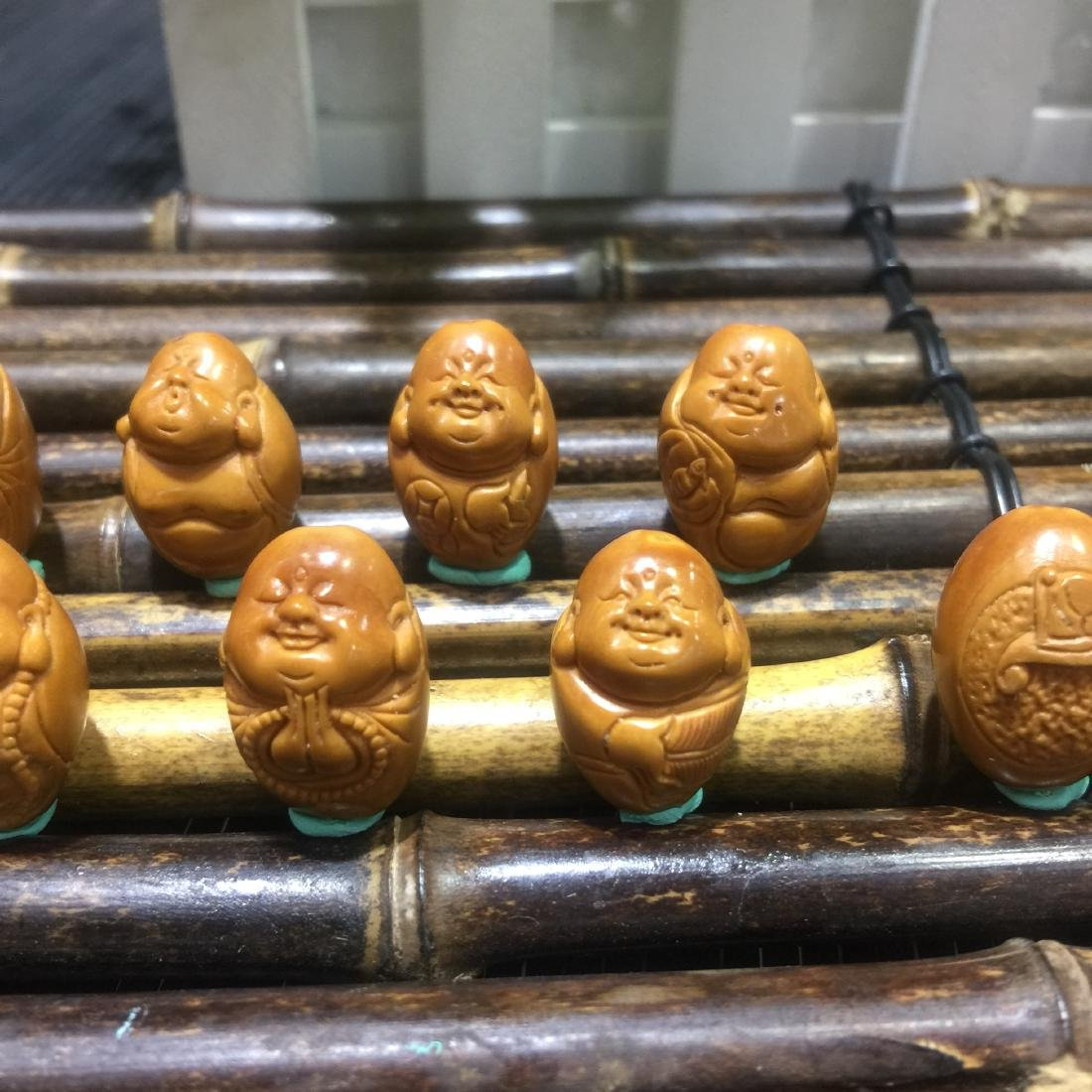 EIGHT OLIVER KENEARL CARVED BUDDHA BEADS - 6