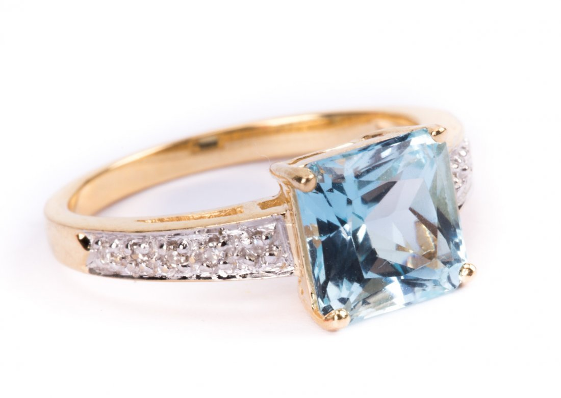 A Lady's Gold Blue Topaz and Diamond Ring