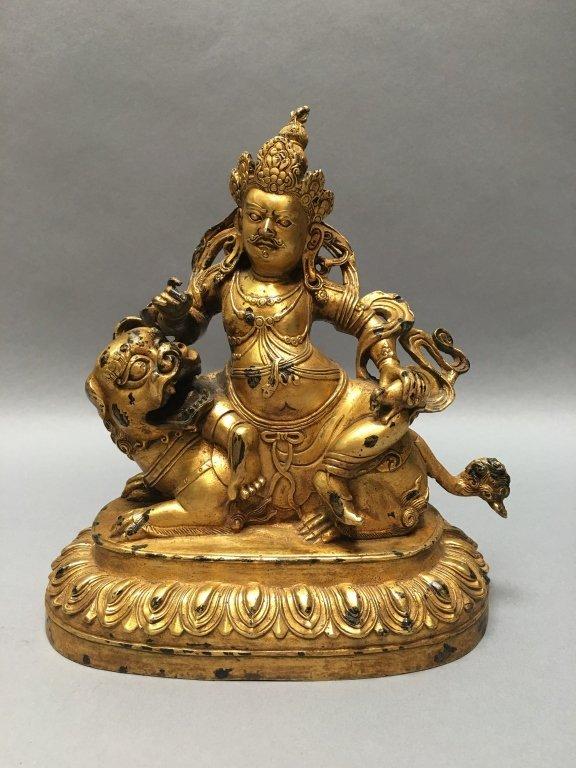 Tibetan gilt bronze figure sitting on foo lion