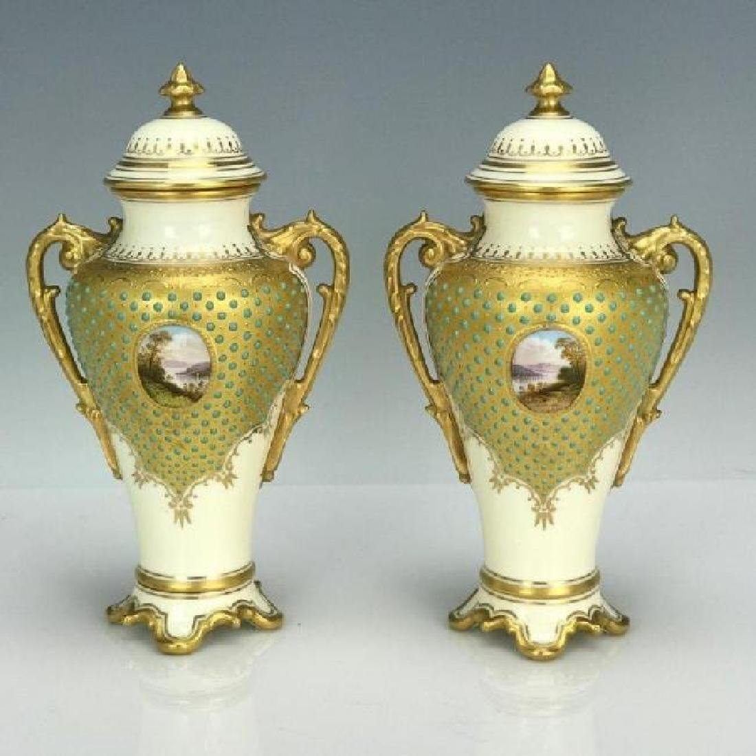 A PAIR OF JEWELED COALPORT VASES AND COVERS