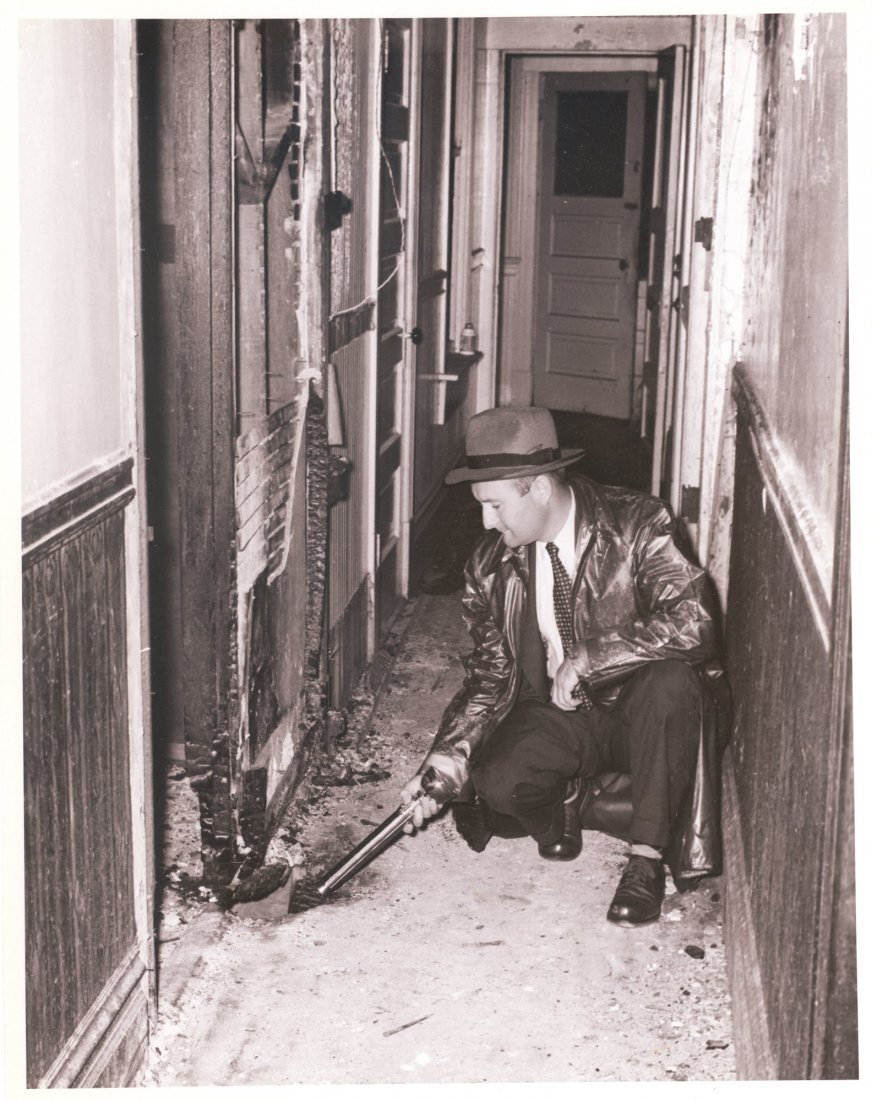 Fire Investigator examines arson scene. c1957