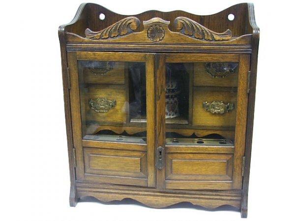 1: A Late Victorian Oak Smokers Cabinet having glazed d