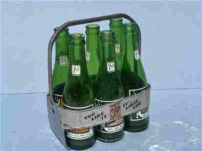A vintage six pack case of 7Up bottles & carrier