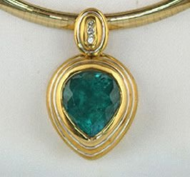 668: Emerald pendant with teardrop shaped stone and 3 r