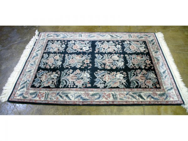"""19: Green and red floral rug.  Size:  80"""" x 48""""."""