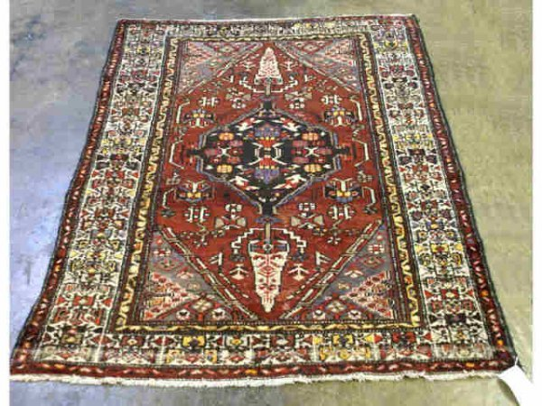 5: Red rug with diamond shaped pattern and black cent