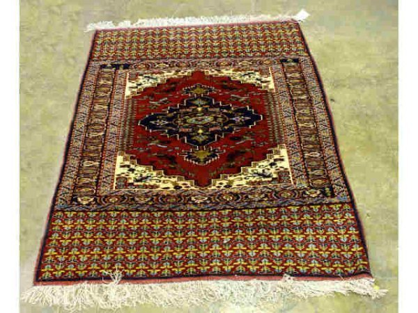 6: Red rug with book end patterned designs.