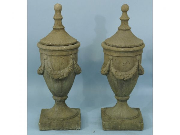 2019: Pair of concrete urns with lids wrapped garland.