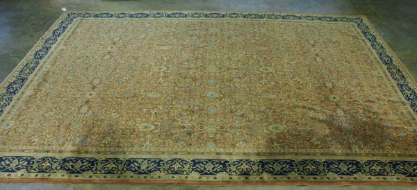 54: A KNOTTED RUG IN NAVY AND RUST IN CAMEL BACKROUND