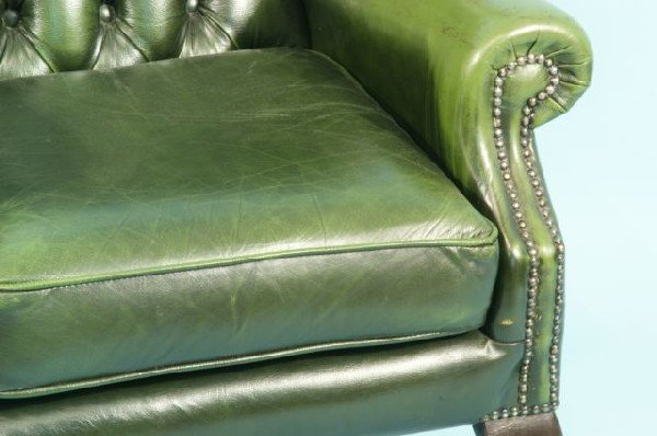 220 BUTTON TUFTED GREEN LEATHER WING CHAIR Lot 220