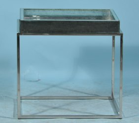 A STAINLESS STEEL OCCASIONAL TABLE WITH A MIRRORED