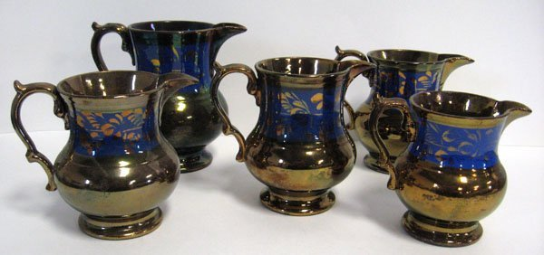 15: Five Copper Lustre pitchers with blue ground bands