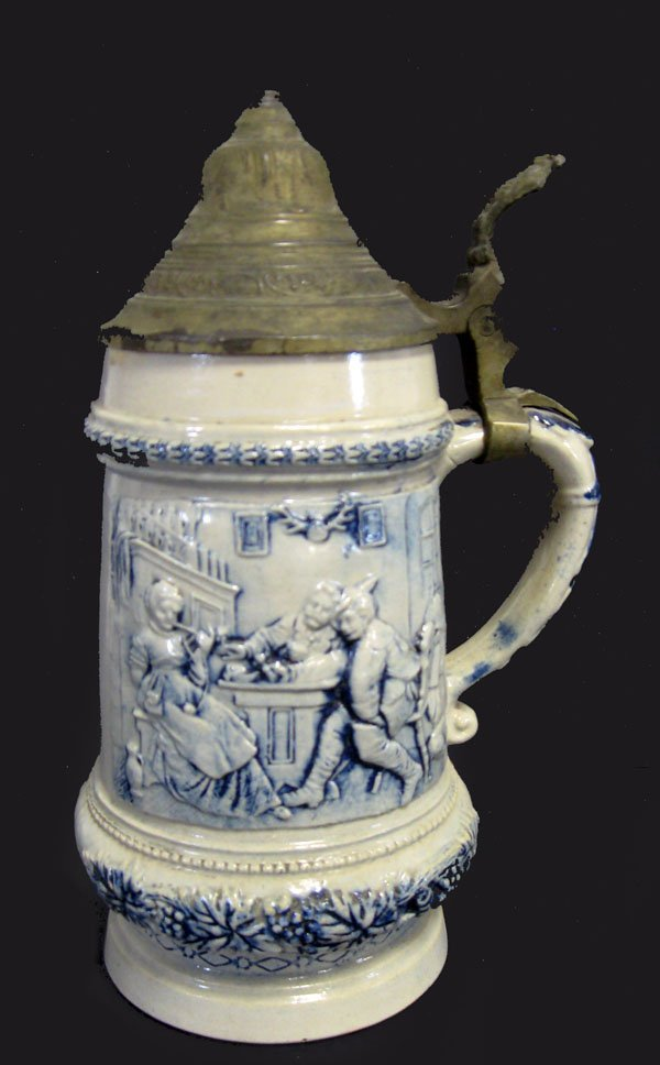 23: Stoneware stein with relief drinking scene and pewt