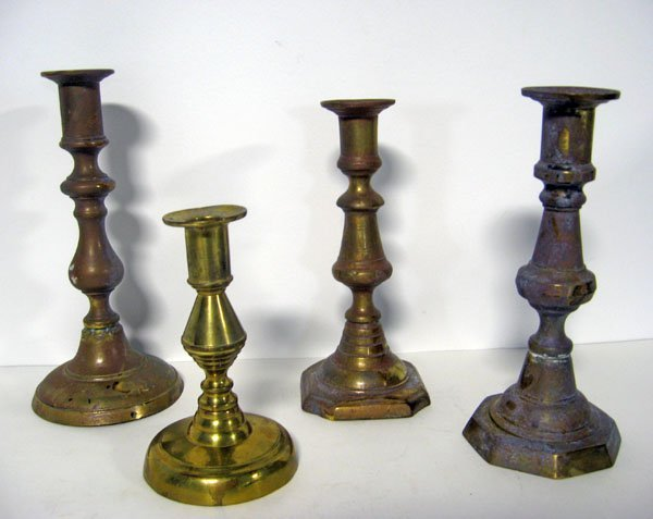 22: Four assorted brass push-up candlesticks. Note plun