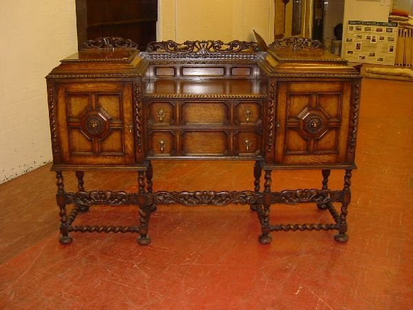 1: A 1930s polished sideboard with carved crown and dra
