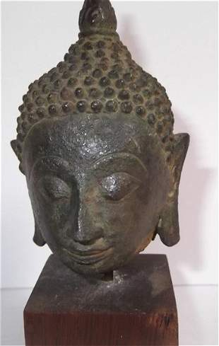Small Buddha head on wood stand