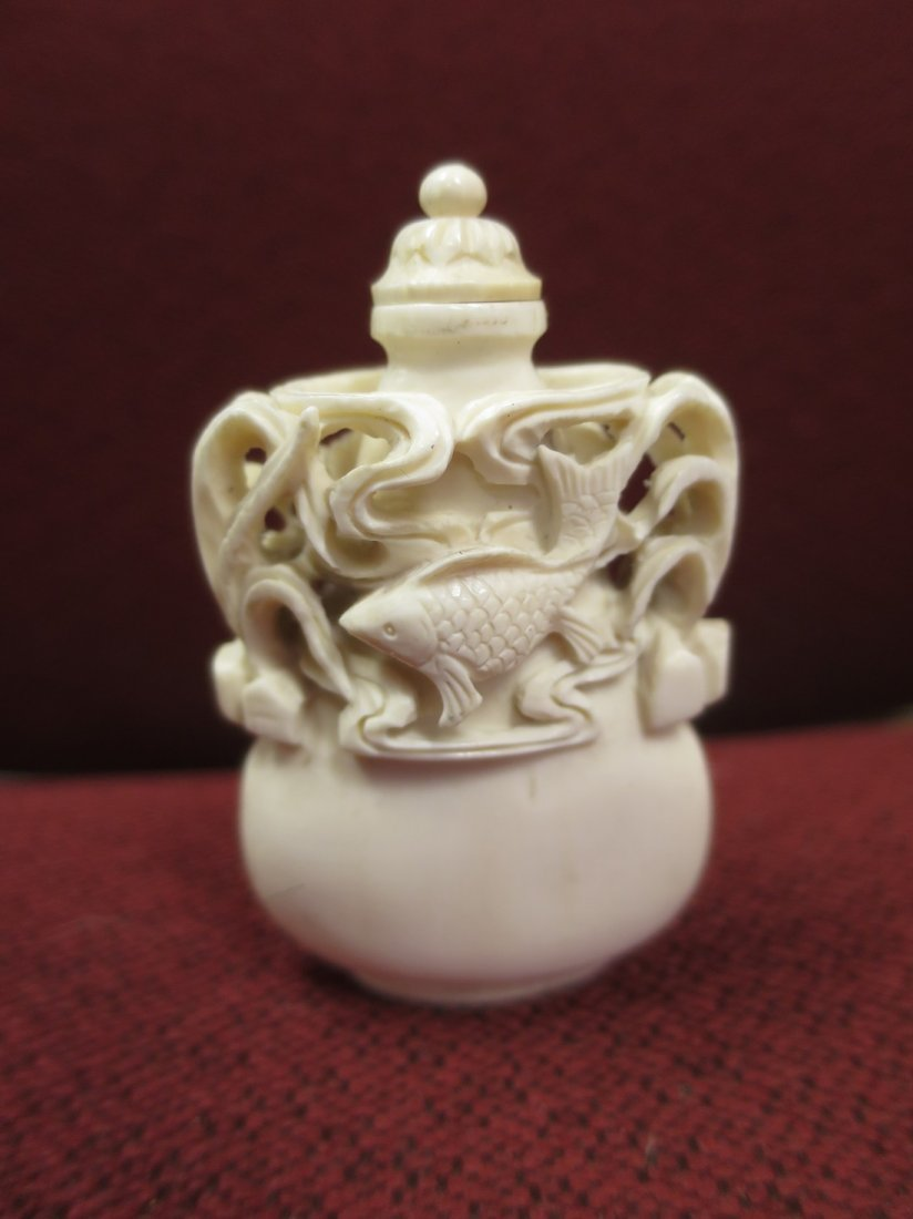 White chinese carved snuff bottle with Koi fish design.