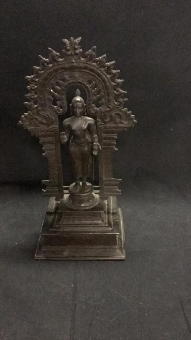 Metal Thai Buddha figure standing under archway