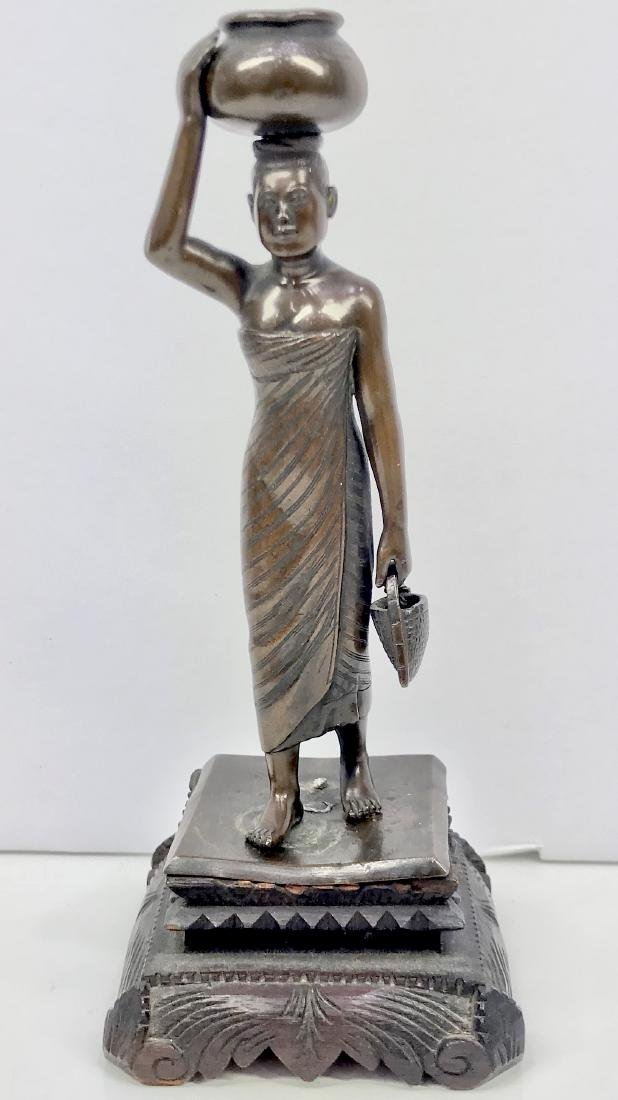 Bronze estatue of woman carrying pot on the head