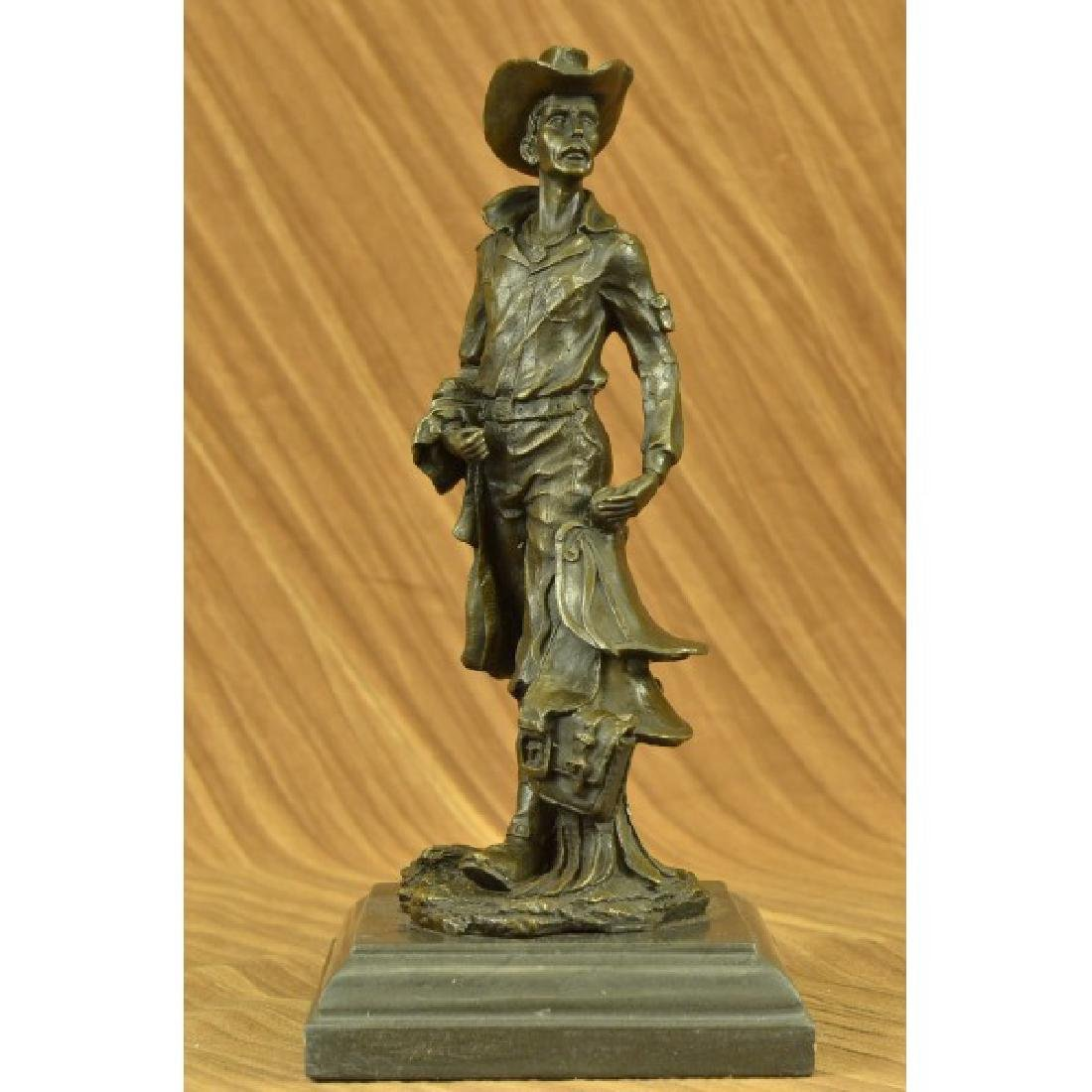 Kamiko Old Cowboy holding his Saddle Bronze Sculpture