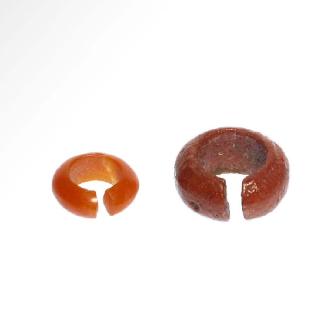Two Egyptian Red Faience and Cornelian Hair-rings, 18th - 5
