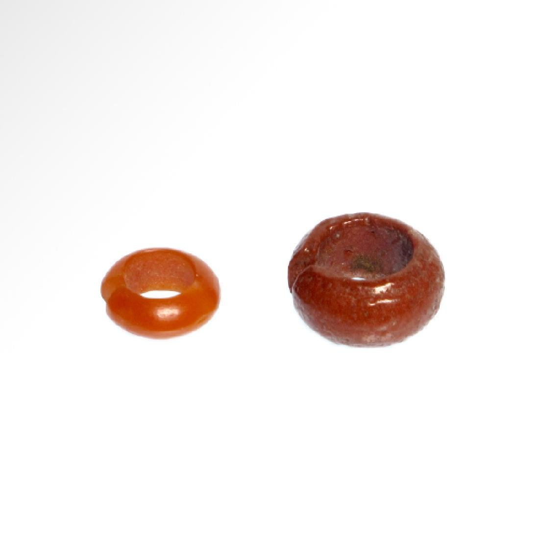 Two Egyptian Red Faience and Cornelian Hair-rings, 18th - 6