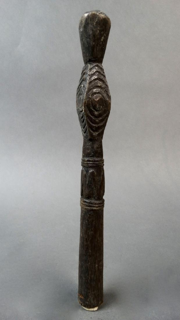 This dark paddle handle has design/ clan motifs on the