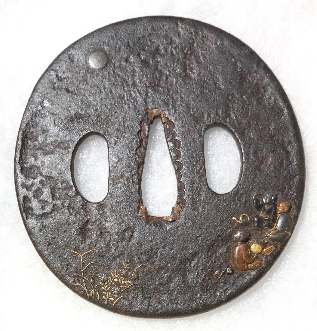 Iron tsuba carved and inlaid with gold, brass, silver,