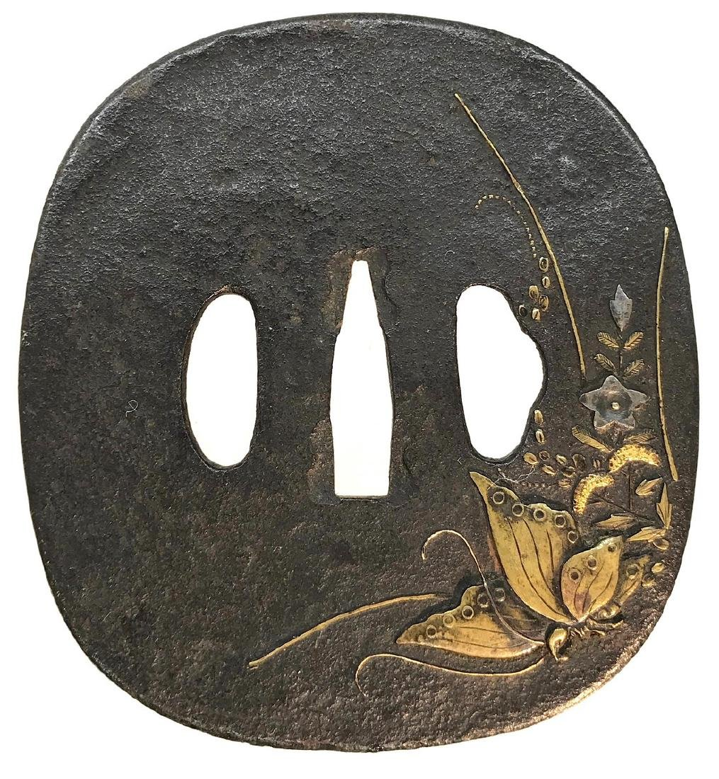 Large iron tsuba with brass, shibuichi, and gold inlay;