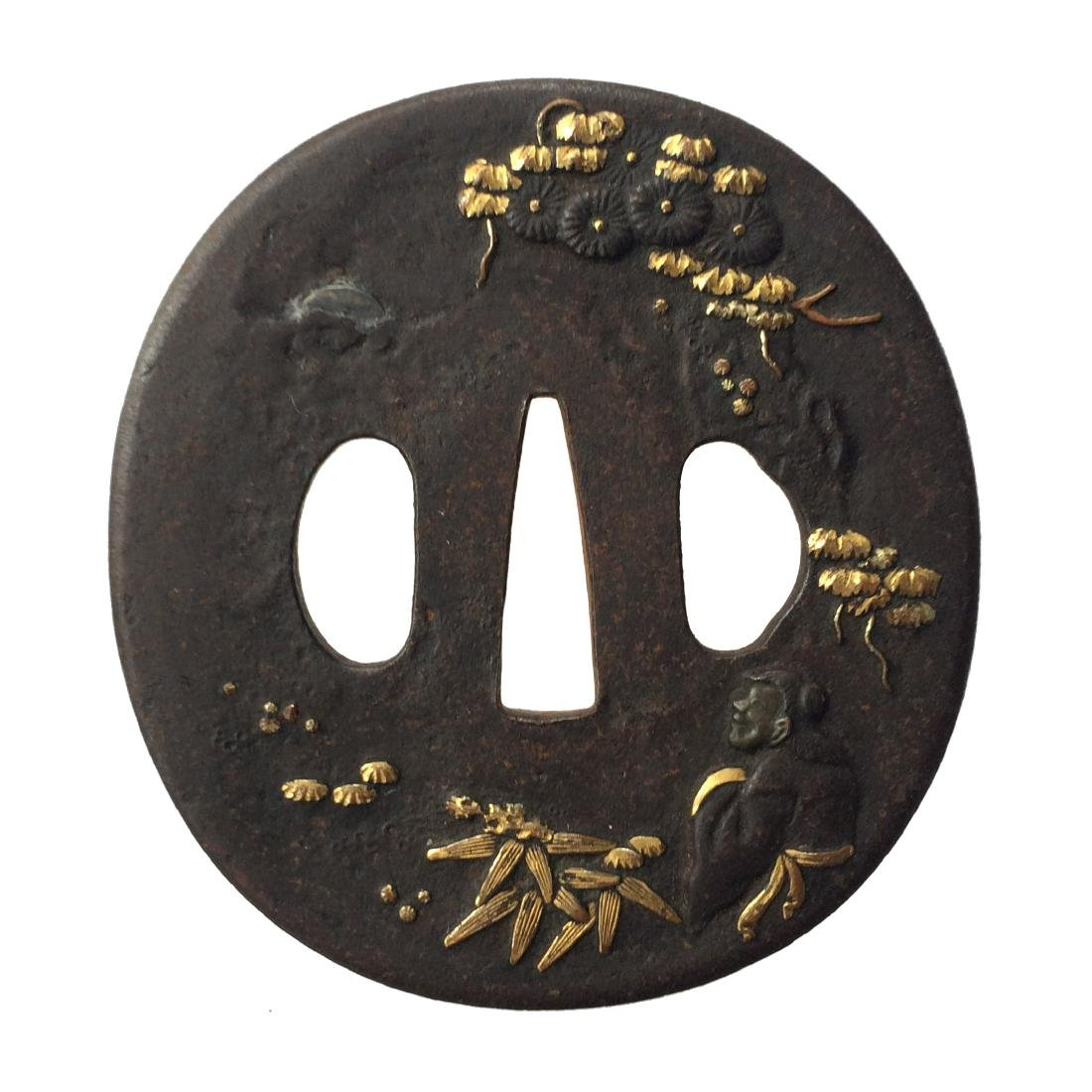 Iron tsuba carved and inlaid with shibuichi and gold