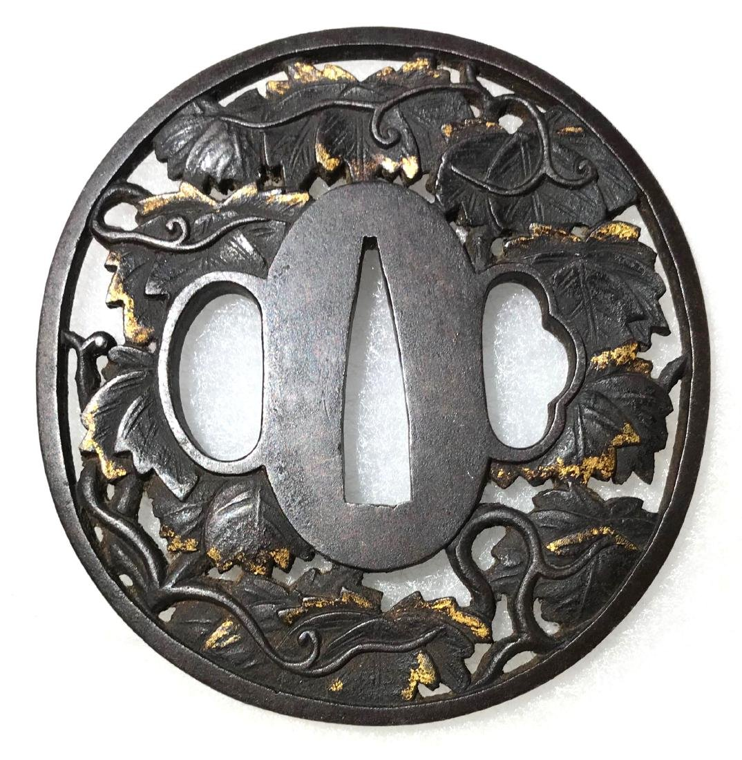 Iron tsuba carved and inlaid with gold