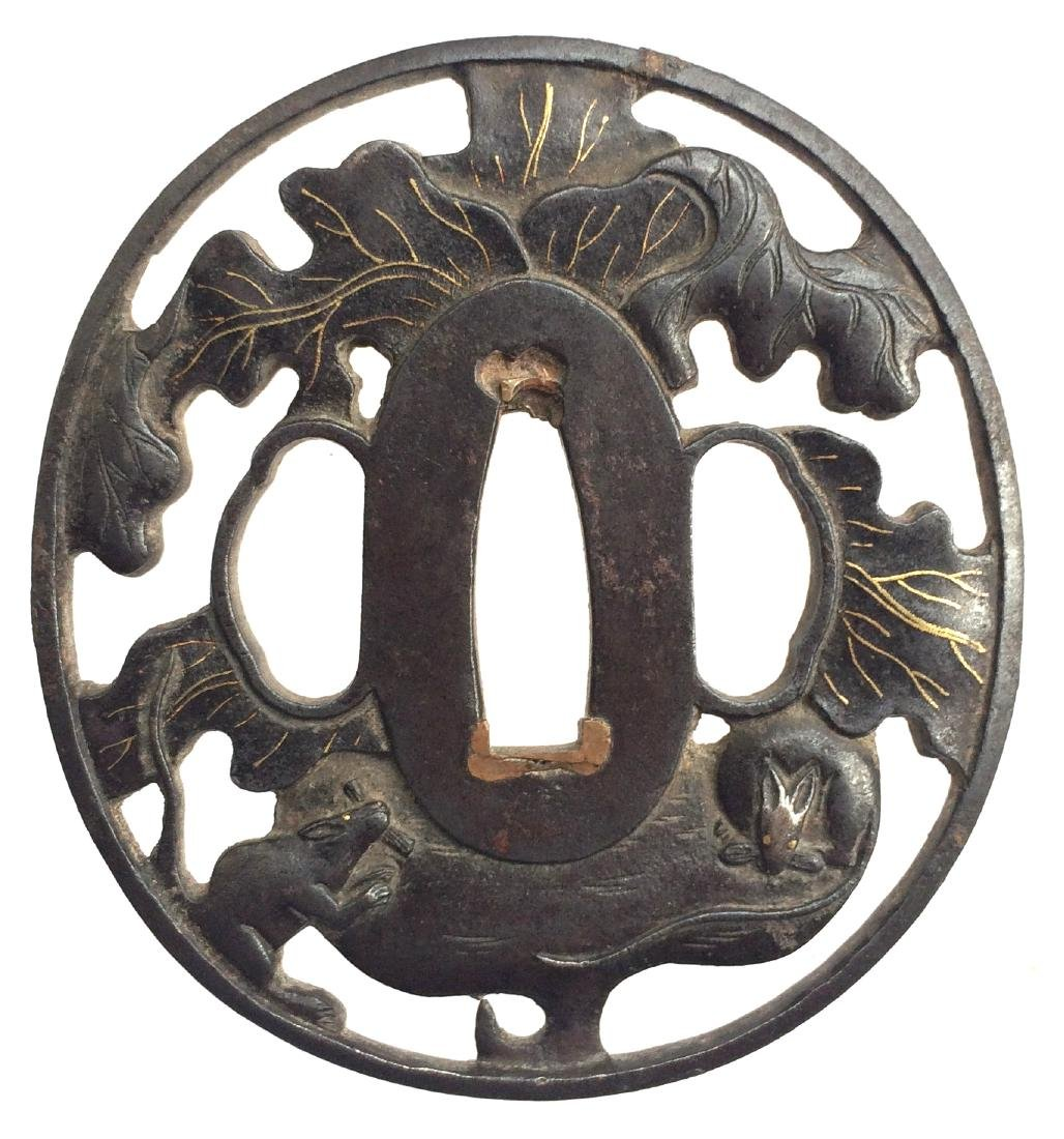 Iron tsuba, pierced, carved and inlaid with gold