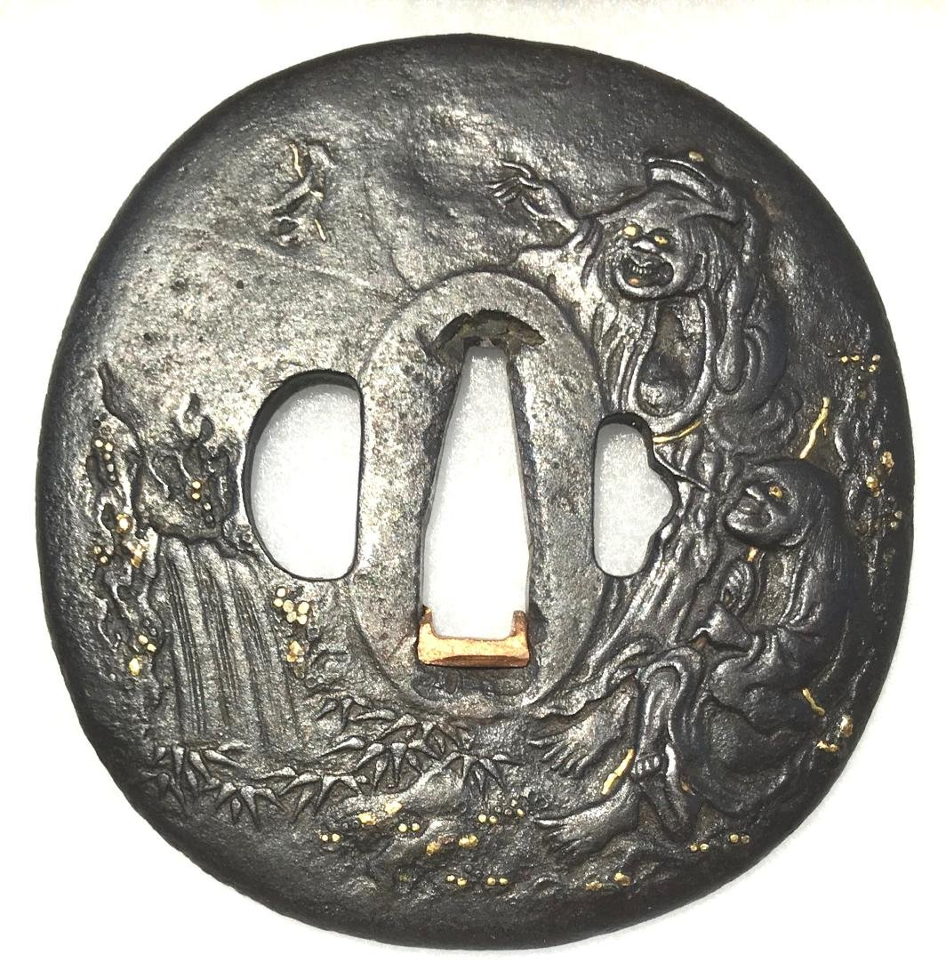 Large iron tsuba with carving and gold inlay