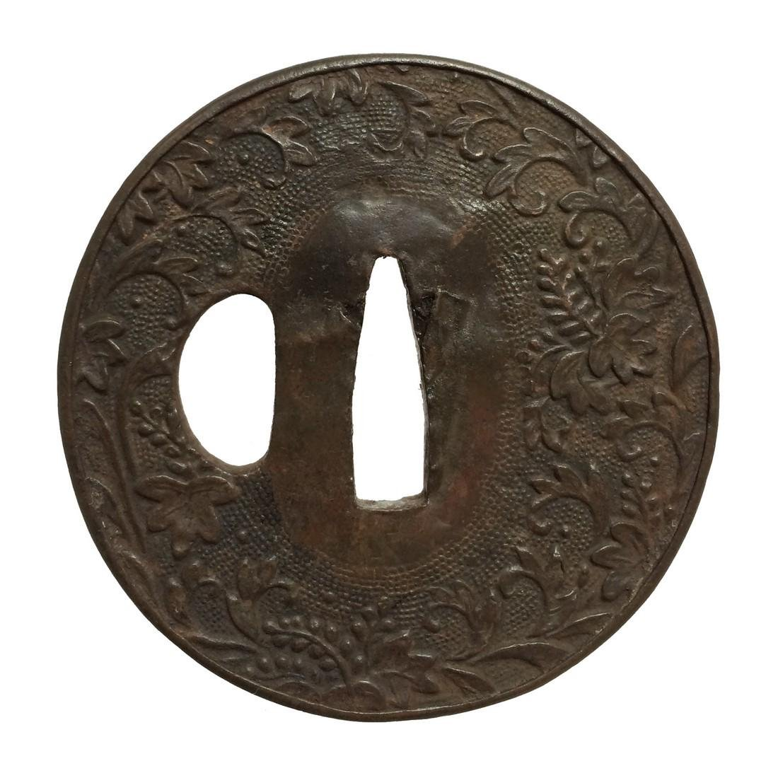Repousse iron tsuba with floral design