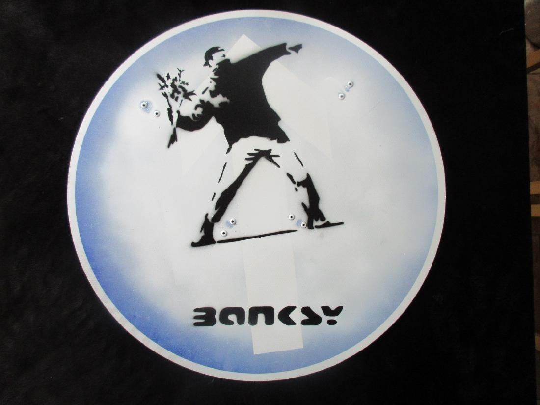 Banksy Flower Thrower spray paint road works sign.