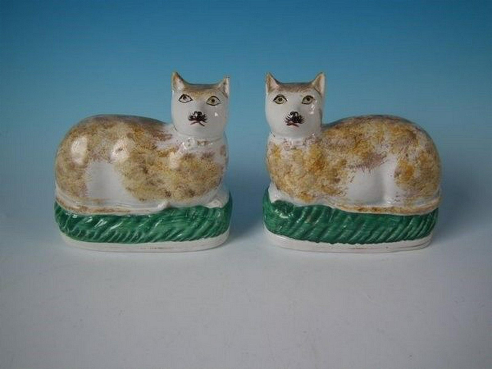 Pair Staffordshire pottery cats, recumbent on cushions