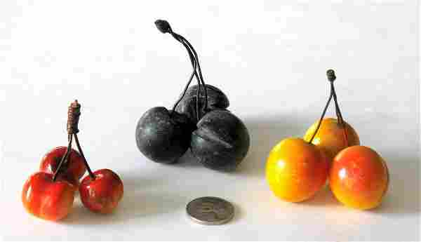 Group of three clusters of stone cherries.