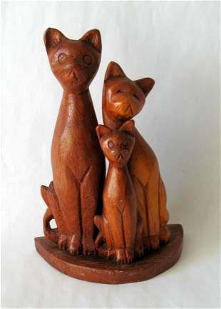 Folk art wood carving of three cats.