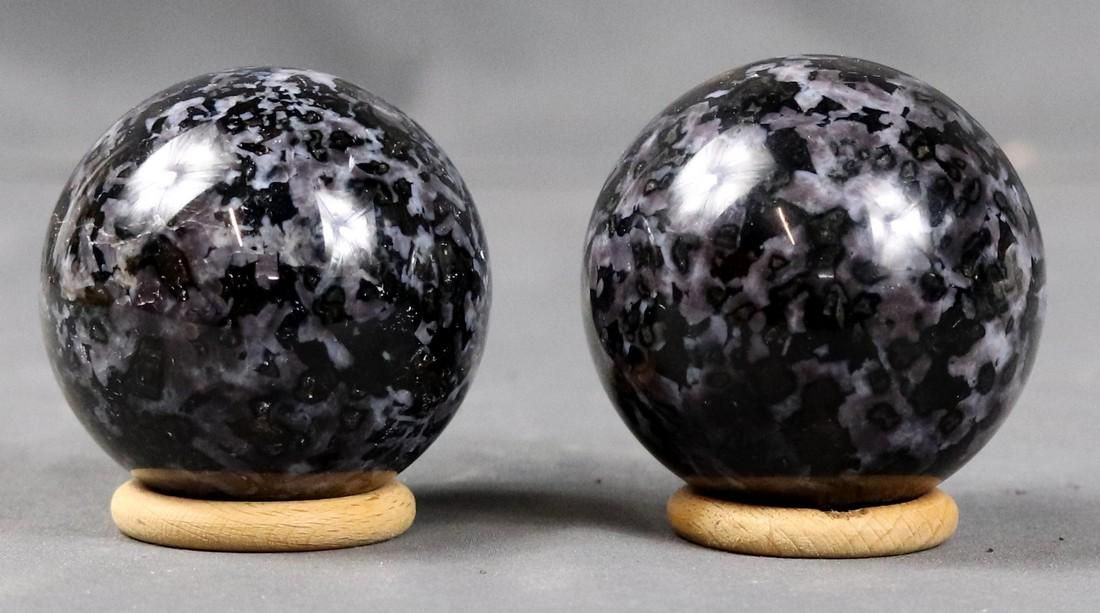 Twin polished Gabbro spheres on wood ring