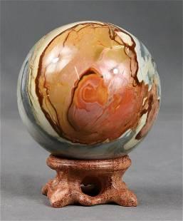 Outstanding polychrom jasper sphere on elegant wood