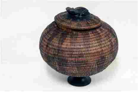 A late 19th century indegenous basket with a wooden