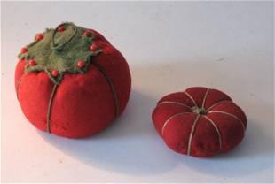 Two vintage tomato pincushions.