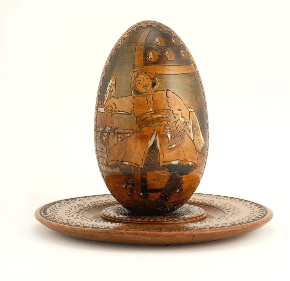 A Russian kustar art carved wood Easter egg & stand