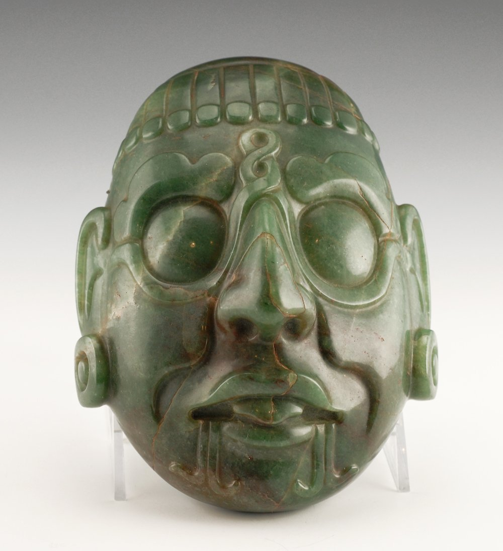 A carved jade mask in Pre-Columbian style