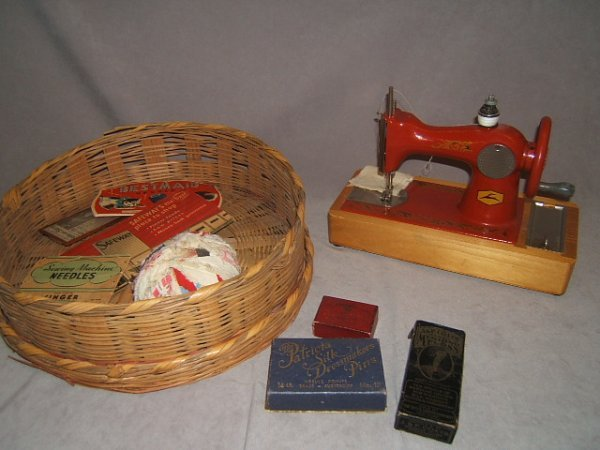 7010: CHILDS SEWING MACHINE AND BASKET OF ITEMS