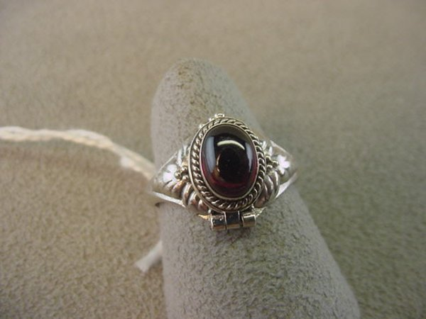 1072: STERLING HINGED POISON RING SET WITH GARNET