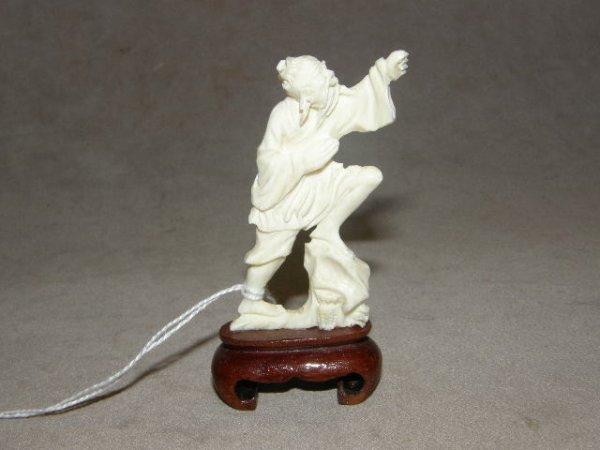 6016: CARVED IVORY FIGURE ON WOOD BASE