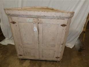 Primitive two-door corner cabinet on casters