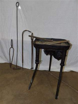 Small 3-legged blacksmith forge with several tongs