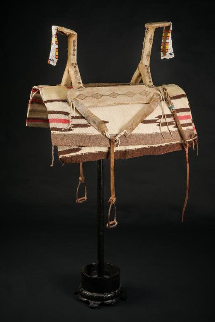 A native's saddle with saddle-pad, stirrups, whip and